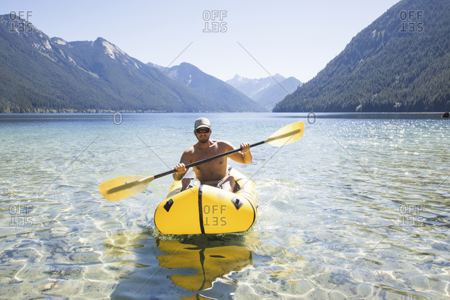 Shirtless man paddling inflatable packraft or kayak.