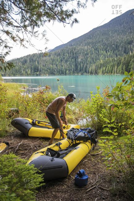 Man on lakeshore, preparing his boats for a packrafting trip at lake.