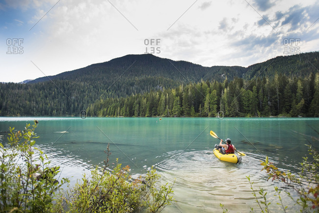 Man paddling inflatable packraft on Cheakamus Lake, Whistler, B.C.