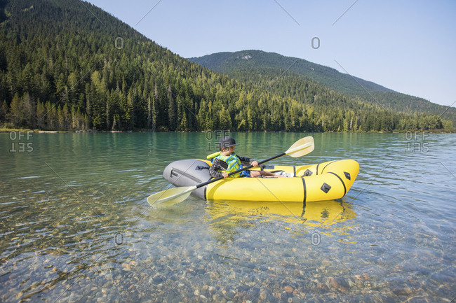 Young boy paddling yellow boat on scenic lake.