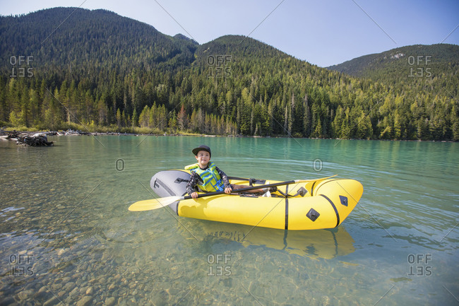 Young boy paddling yellow packraft boat on scenic lake near Whistler.