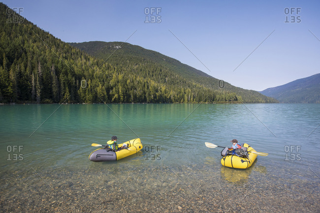 Two young boys learning how to paddle kayak on scenic lake.