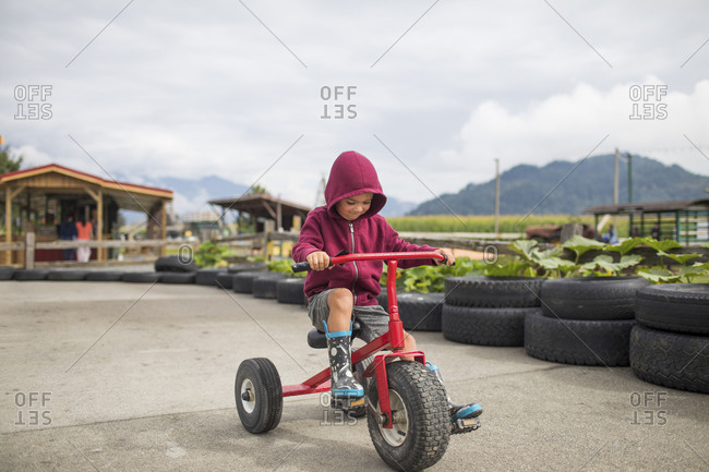 Young boy wearing hoody pedals oversized tricycle on racetrack.