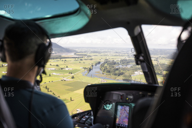 Helicopter pilot looking out at farmland in the Fraser Valley.