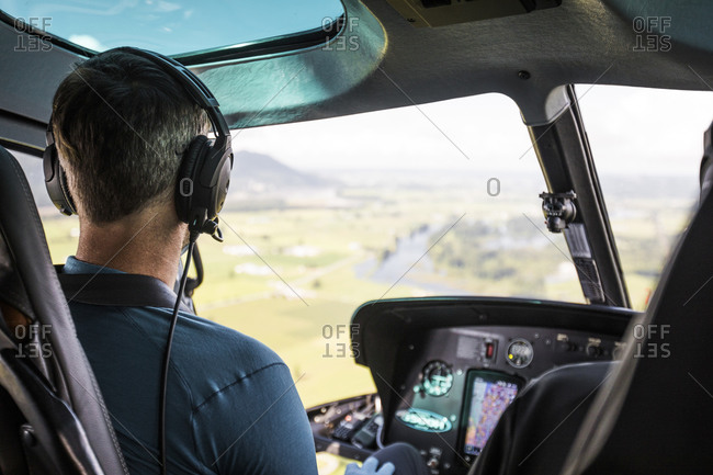 Helicopter pilot flying high above farmland below.