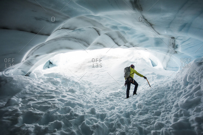 Climber explores an ice cave on a mountaineering trip.
