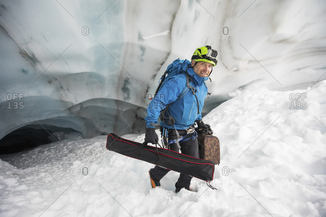 Scientist carries gear out of a glacier cave, British Columbia, Canada