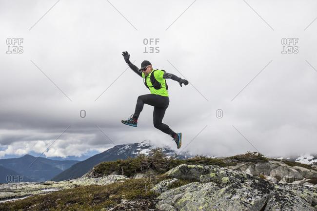 Trail runner jumps off rocks on mountain ridge.