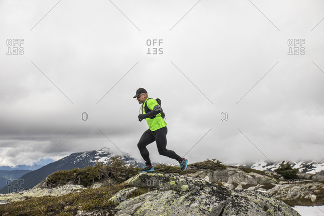 Side view of fit active man trail running on mountain ridge.