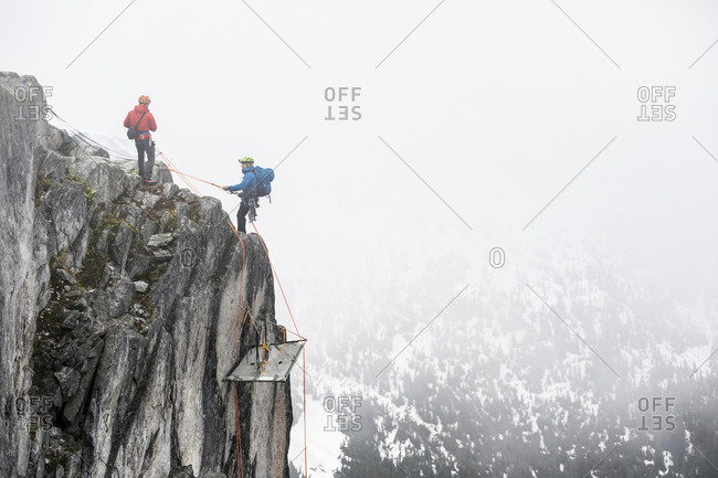 Climbers rappelling onto portaledge on a vertical cliff face.
