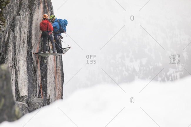 Two climbers standing on portaledge, setting up camp for night.