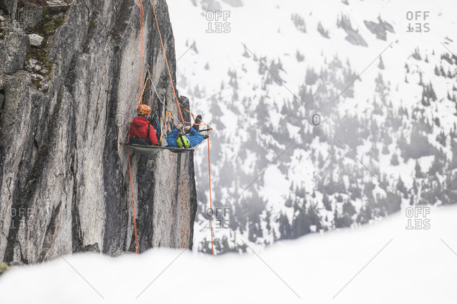 Rock climbers rest on a portaledge during a multi-day climbing trip.