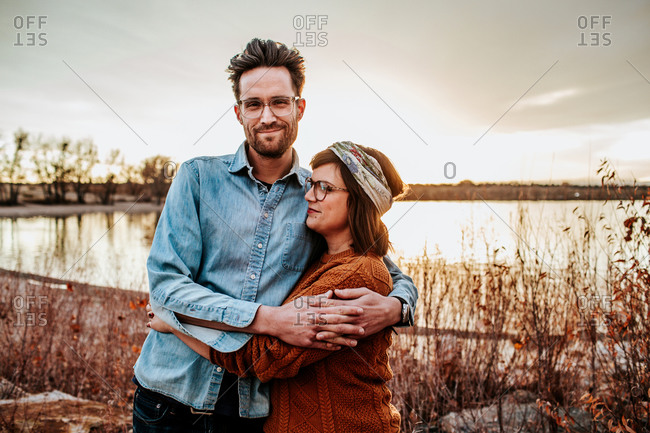 Happy couple hugging near a lake in Denver CO on a autumn evening