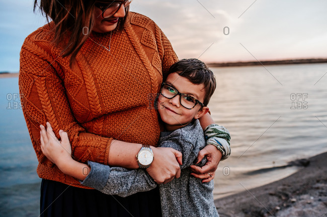 Mom hugging young son on the shore of a lake on a autumn evening