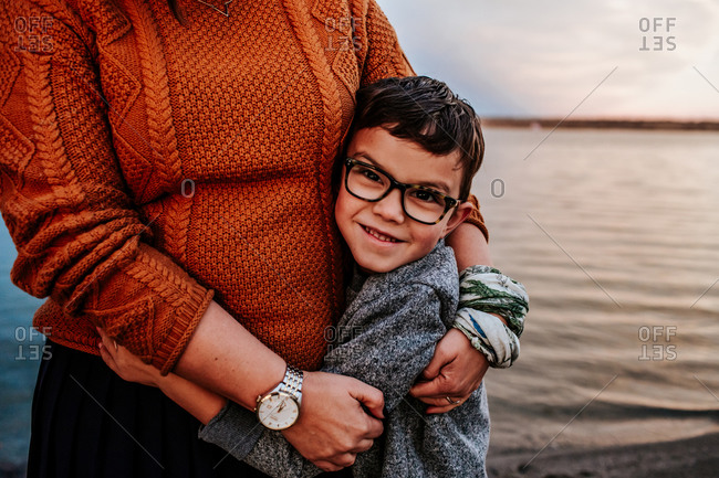Happy young boy hugging mom near a lake on a autumn evening