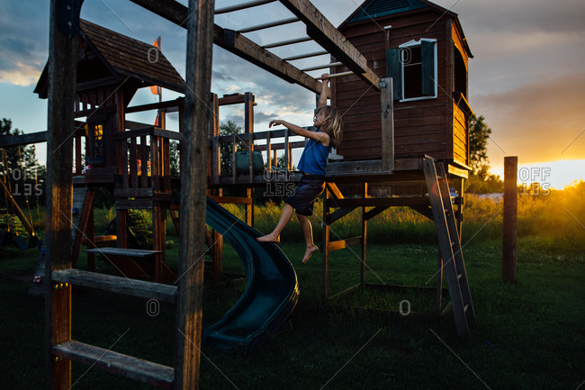 Young boy on play center at sunset