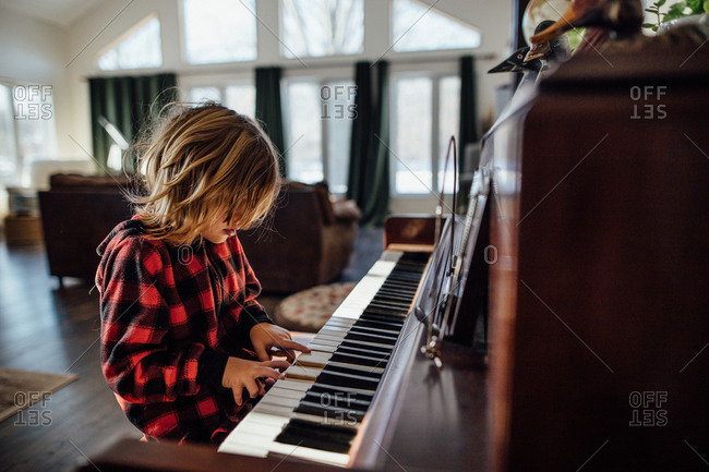 Little boy with messy hair playing the piano