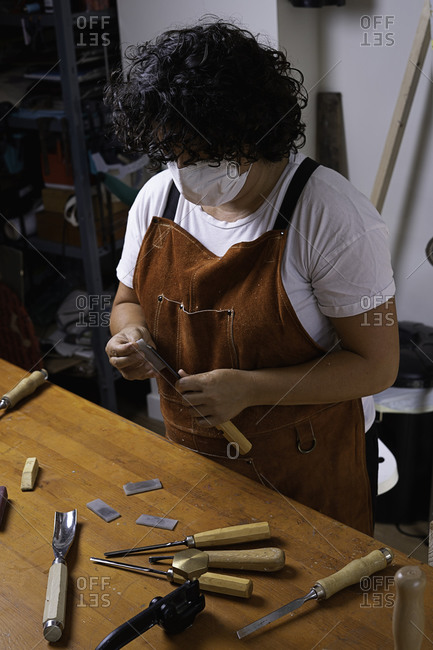 Wood craftswoman with mask sharpening tool with stone