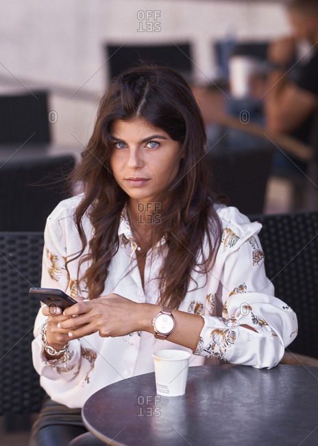 Young woman uses her phone on the terrace of a bar