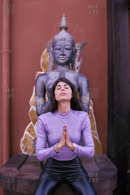 European woman practicing Buddhism in front of a Buddha figure