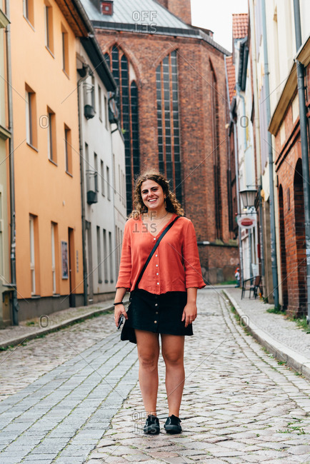 Joyful young woman standing in the street of an old European town