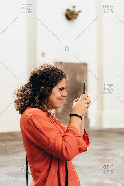 Joyful young woman taking pictures with her smartphone