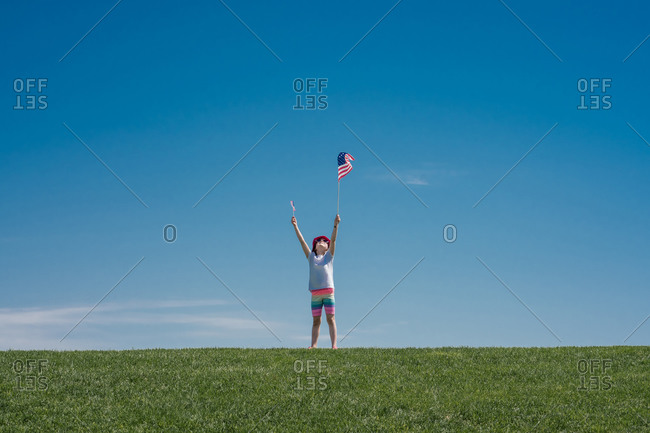 Young girl holds 2 American flags over her head on a green grass hill