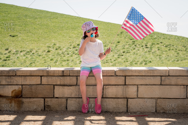 Young girl holds an American flag while eating a red and blue popsicle
