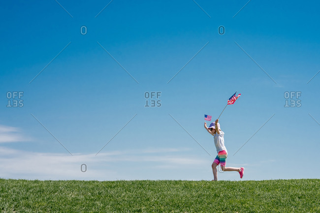 Young girl leaps across a grass hill waving 2 American flags