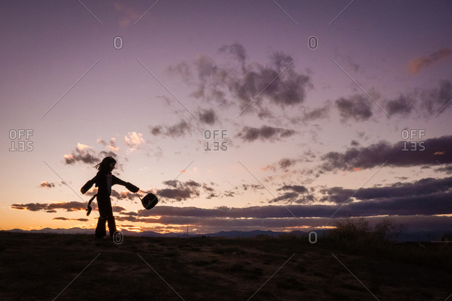 A young girl a twirls a Halloween bucket on top of a hill at sunset