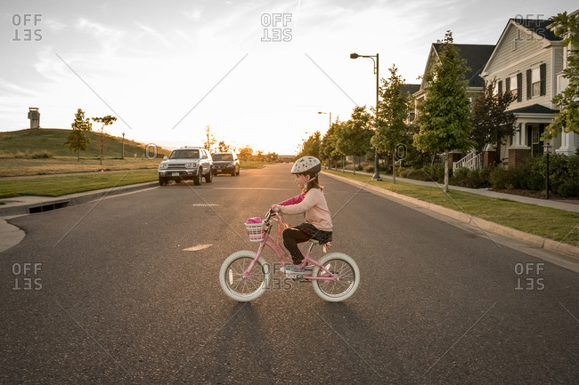 Young girl rides a bike across the road at sunset