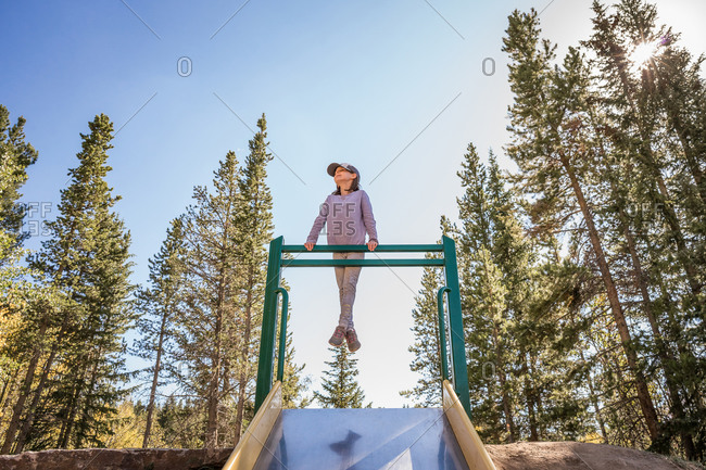 Smiling young girl plays on a playground slide among tall pine trees