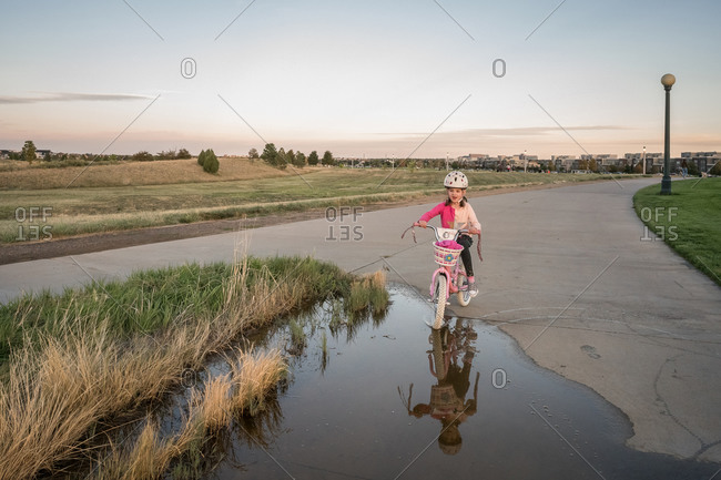 Playful young girl bikes through a puddle of water in a park