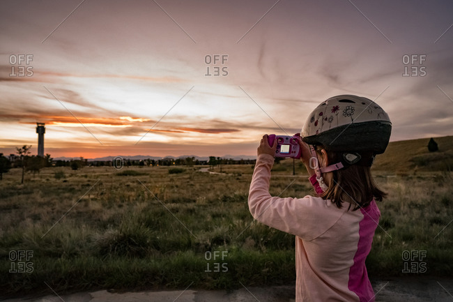 Young girl takes a photo of the sunset and the mountains