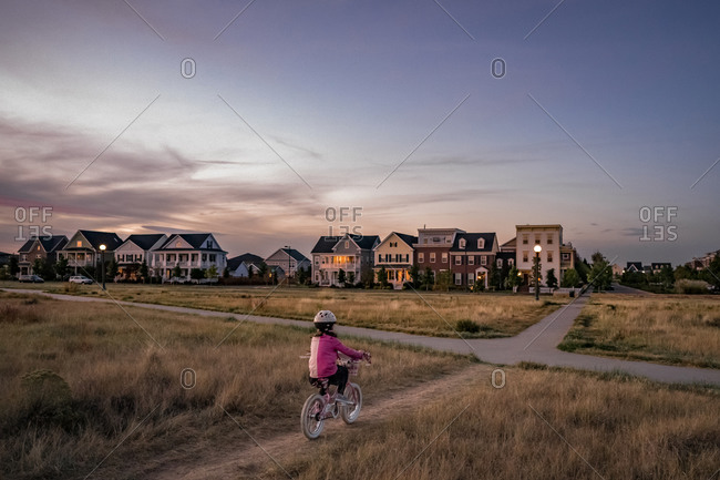 Young girl bikes on a park dirt path on the edge of a neighborhood