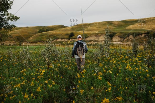 Man walking through tall grass to fish