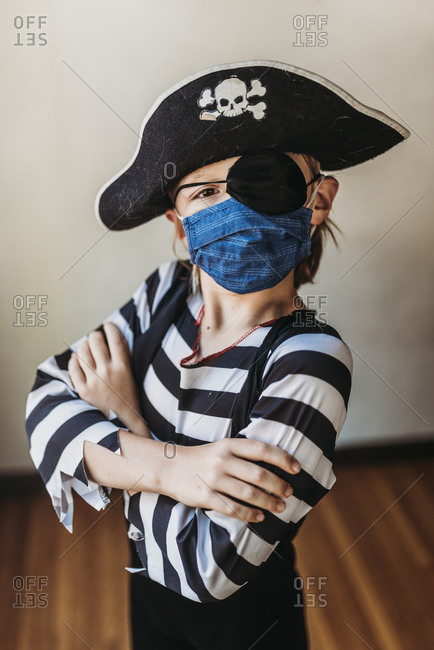 School age young boy dressed as pirate with face mask on