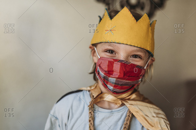 School aged young boy in dressed as king with face mask