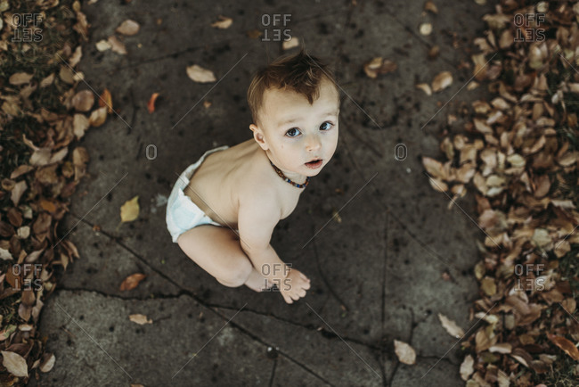 Baby toddler boy in diaper sitting with fall leaves at Halloween