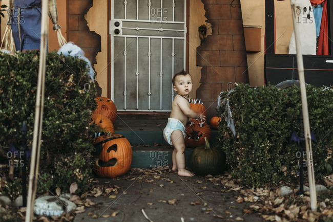 Baby toddler boy in diaper with Halloween decorations during fall
