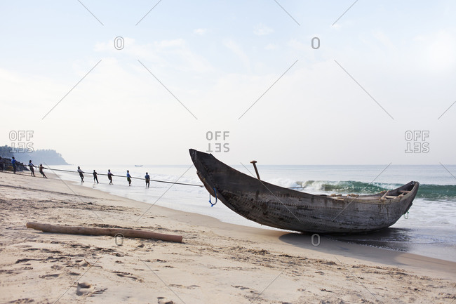 Indian fishermen pull up nets from the sea
