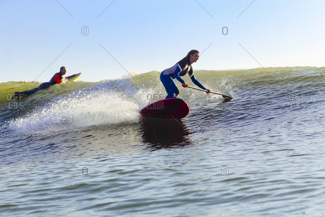 Female SUP surfer at sunset time