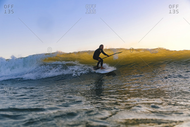 Male sup surfer at sunset time
