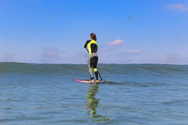 Female SUP surfer on a wave