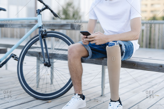 Disabled bicyclist browsing smartphone in city