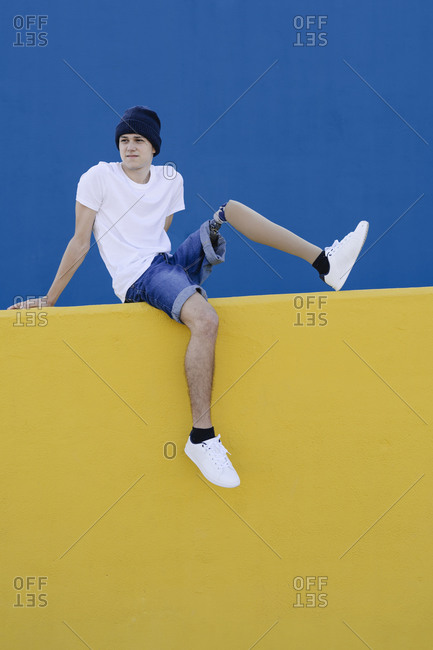 Handicapped teenager sitting on fence