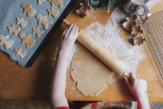 Young girl rolling out gingerbread dough with a rolling pin