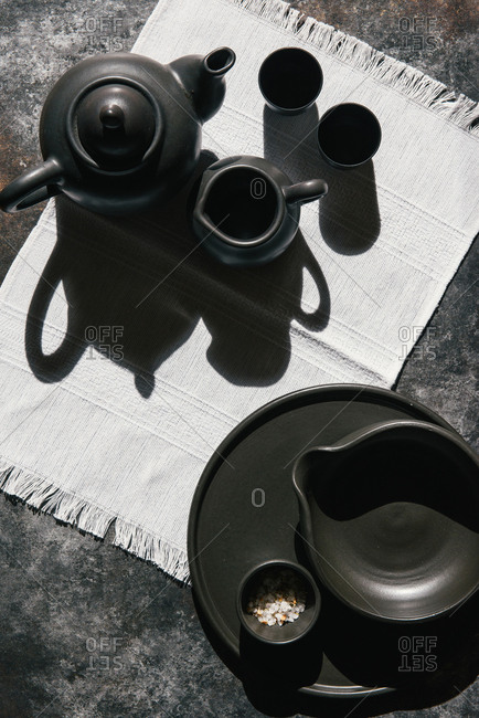 Overhead view of black clay tea pots and cups on linen and black board