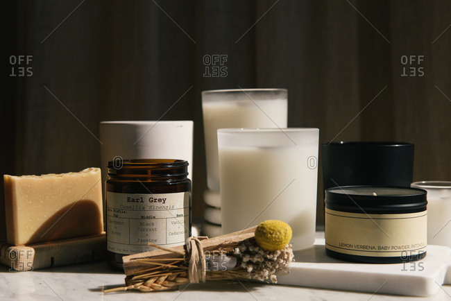 Side view of home beauty products of candles, soap and palo santo