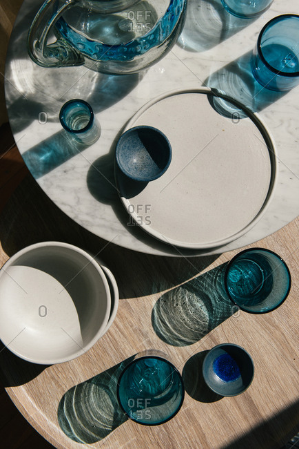 Overhead view of blue glass and ceramics on marble and wood tables
